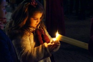 A young girl collects wax from a blessed candle during the processions of Semana Santa.